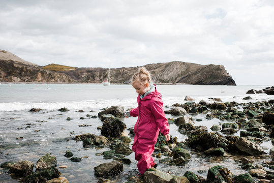 blonde girl walking on rocks at the beach at lulworth cove, England