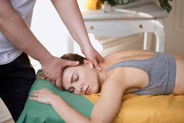 masseur works. man makes a beautiful woman massage