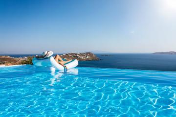 Frau mit Sonnenhut im Bikini treibt auf einer Lufmatratze im Infinity Pool und genießt die Aussicht auf das Meer im Sommer
