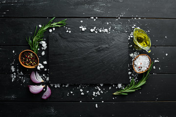 Fotomurales - Cooking banner. A stone plate. Top view. On a black background. Free copy space.