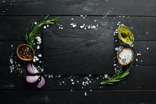 Cooking banner. A stone plate. Top view. On a black background. Free copy space.