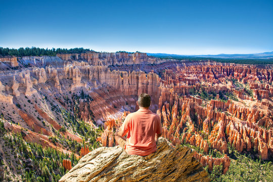Man sitting on top of the mountain looking at beautiful view. Boy relaxing on rock on summer vacation hiking trip. Man meditating in nature. Inspiration Point. Bryce Canyon National Park,Utah,USA