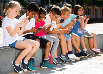 Eight kidsare chatting on their smartphone on walking