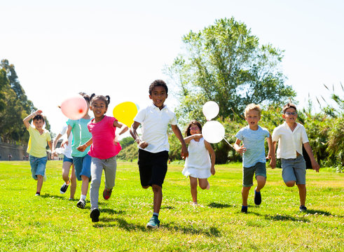 Cheerful kids with balloons are jogging together in the park and having fun