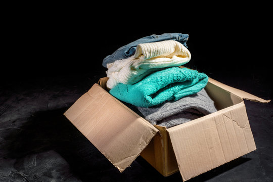 Donation concept. Donation box with donation clothes on a dark background. Charity. Help for people in need