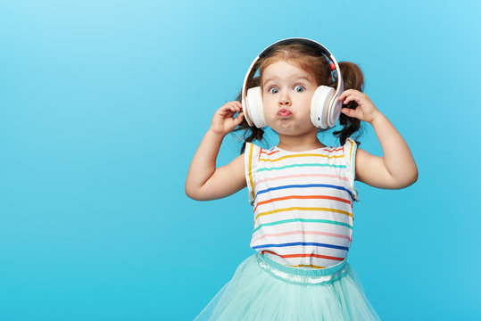 Happy smiling child enjoys listens to music in headphones over colorful bleu background. Vivid and fun emotions, happy child with pleasure listens to songs in wireless headphones