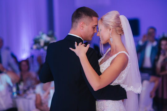 Portrait of first dance of stylish wedding couple. Handsome groom and elegant bride in the restaurant