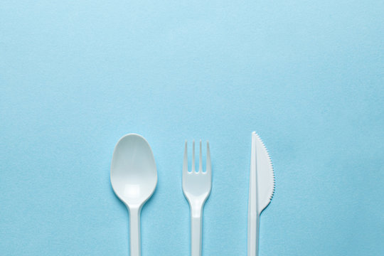 Plastic cutlery, forks, spoons and knives. Pollution of the environment with plastic and microplastics. Blue background. Copy space for text.