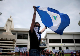 A masked demonstrator holds a national flag during a march to commemorate the National Student Day and to protest against Nicaraguan President Daniel Ortega's government inside of Central American University (UCA) in Managua