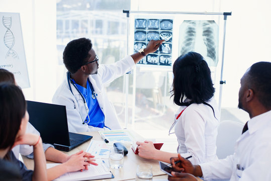 Afro American doctor shows and explains MRI results to his professional team. Group of international doctors or interns have a meeting and making notes at hospital room. Health care concept.