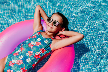beautiful teenager girl floating on pink donuts in a pool. Wearing sunglasses and smiling. Fun and summer lifestyle