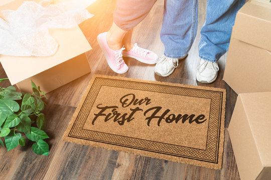 Man and Woman Unpacking Near Our First Home Welcome Mat, Moving Boxes and Plant