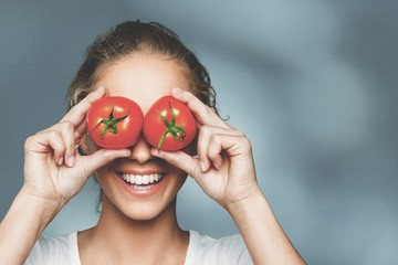 Canvas Prints Textures Beautiful laughing woman holding two ripe tomatoes
