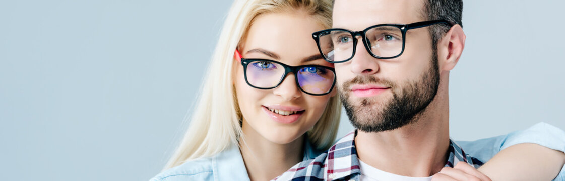 panoramic shot of man and beautiful girl in glasses isolated on grey
