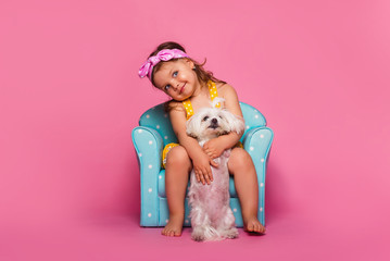Little girl with a dog. A cute little girl with a dog is sitting in a blue armchair. Pink background