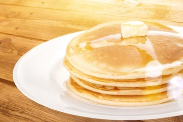 Stack of tasty pancakes with butter on a white plate
