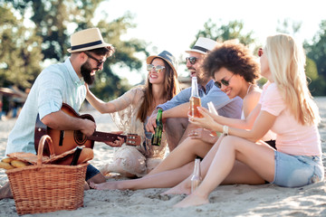 Young people with guitar on the beach