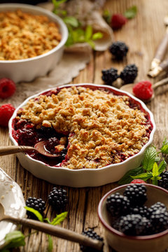 Crumble, Mixed berry (blackberry, raspberry) crumble, stewed fruits topped with crumble of oatmeal, almond flour, butter and sugar  in a baking dish on a wooden table, close-up