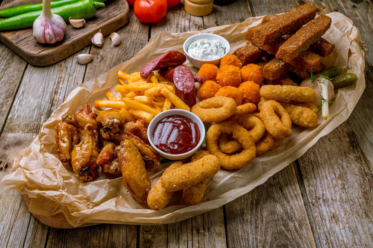 assorted beer snacks on the board with sauses on wooden table