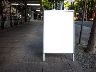 Blank white outdoor advertising stand/sandwich board mock up template. Background texture of clear street signage board placed outdoor on pedestrian sidewalk. Urban city environment.