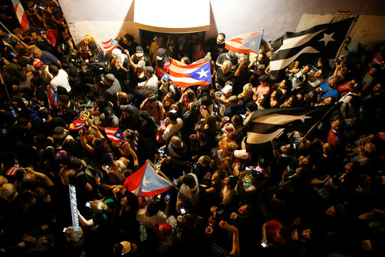Demonstrators chant slogans as they wave Puerto Rican flags during ongoing protests calling for the resignation of Governor Ricardo Rossello in San Juan