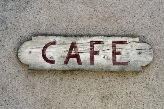 Close shot of a wooden cafe sign nailed on a wall