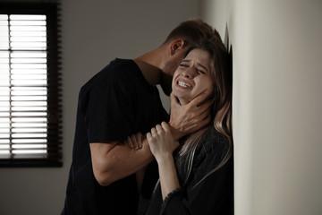 Obraz Man choking young woman indoors. Stop sexual assault - fototapety do salonu
