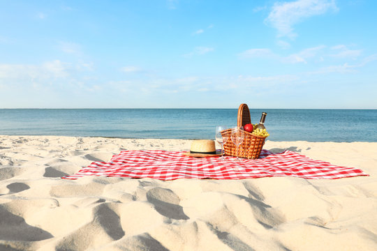 Checkered blanket with picnic basket and products on sunny beach