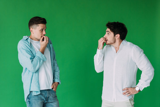 two worried men biting fingers and looking at each other isolated on green