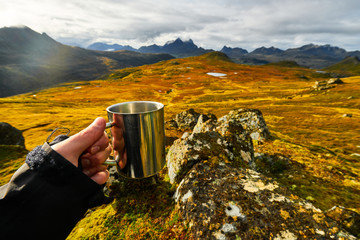 Man holding a cup of coffee with golden landscapes in the background on Lofoten Islands