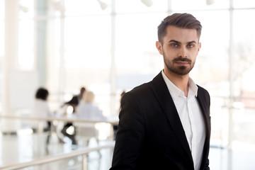 Head shot portrait confident businessman in suit posing in hallway