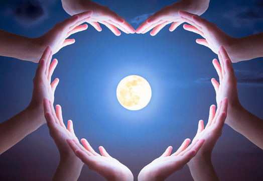 International Day of Friendship concept: hands in shape of heart on moon  background