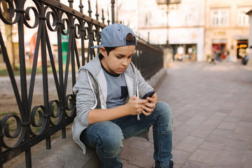 Young boy play online game at smartphone outside. Boy sitting in centre of the city. Boy play games while his mom going to the shop