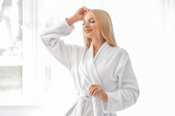 Wall Mural - Beautiful young woman in bathrobe at home