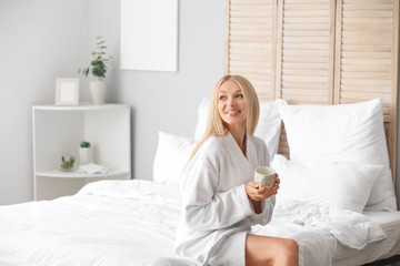 Wall Mural - Morning of young woman drinking coffee in bedroom