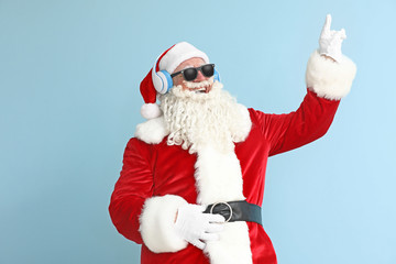 Portrait of cool Santa Claus listening to music on color background