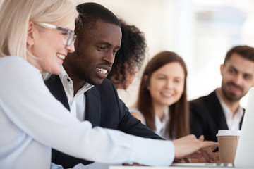 Focused smiling diverse colleagues using laptop together close up