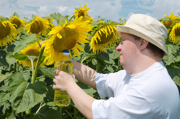 Young man with down syndrome as a farmer holding bottle of sunflower oil. Beatiful sunflower field
