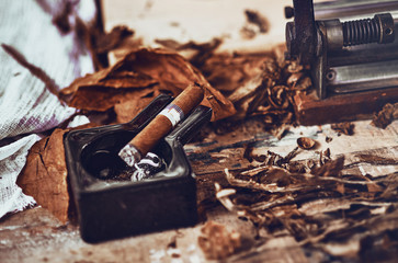 close up of a Cuban cigar and a black ceramic ashtray on the wooden table whit dried and cured tobacco leaves.