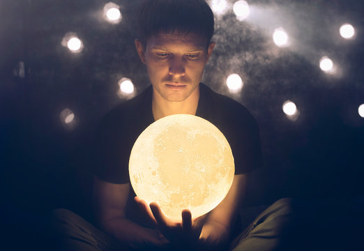 Man holds a yellow moon in his hand