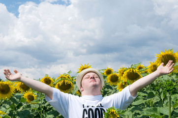 Young man standing with arms wide open in the sunflower field. Happy man with down syndrome in the countryside