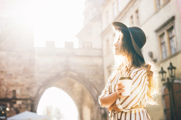 Beautiful woman in brown hat drinking coffee outdoor. Young stylish woman drinking coffee to go in a city street. Wall mural