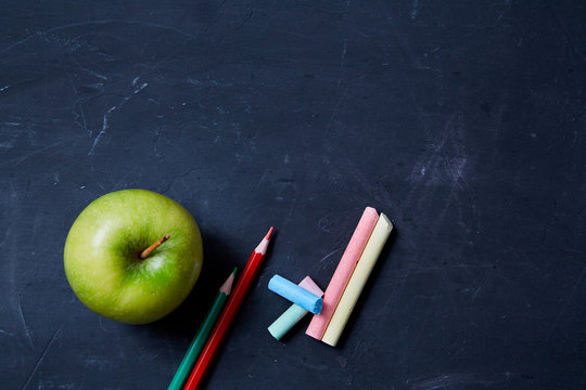 Back to school or student and education concept. Top view. Apple, crayons and school accessories
