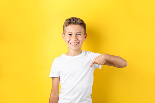 Boy in t-shirt against yellow background, space for text