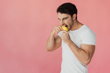 hungry muscular man in white t-shirt eating banana isolated on pink Wall mural