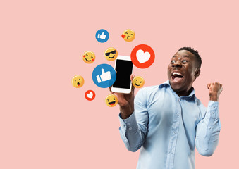 Fototapeta Social media interactions on mobile phone. Internet digital marketing, Chating, commenting, liking. Smiles and icons above smartphone screen, that holding by young man on pink studio background. obraz