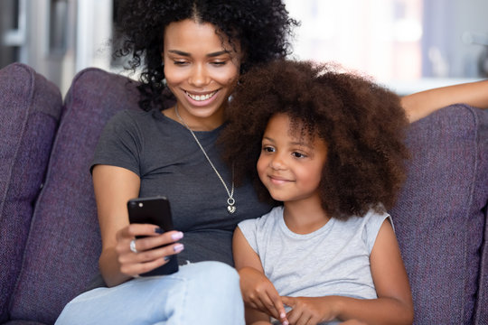 Cheerful mother little daughter spending time at home using smartphone