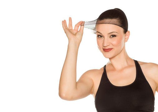Young beautiful woman posing with wig cap on white background