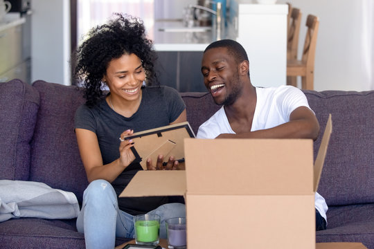 African couple unpacks belongings on moving day at new house