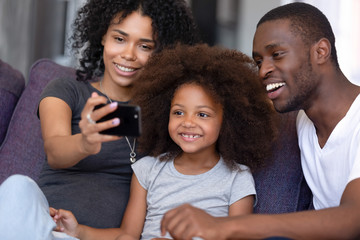 Cheerful african family with kid take selfie photo using phone